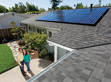 arial shot of couple in front of home with solar panels on the roof - Improve the value of your home