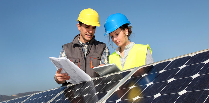 Two solar specialists discussing producing electricity from solar energy over a solar panel