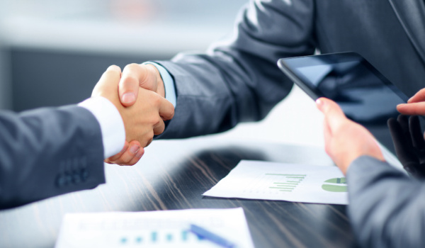 Men shaking hands over a table with papers